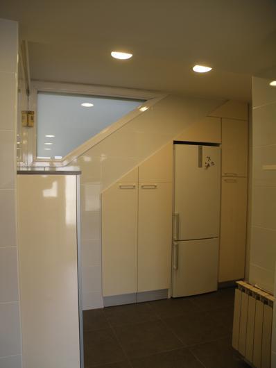 Reforma de baño con armarios y frigorífico bajo escalera